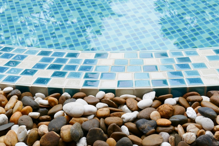 You can place small beach pebbles around the pool landscaping.
